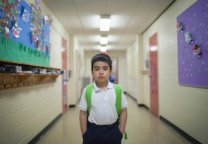 School boy standing in hall at school